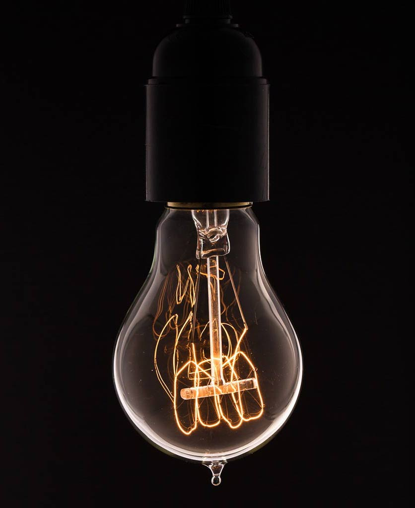 traditional quad loop filament vintage style light bulbs against black background