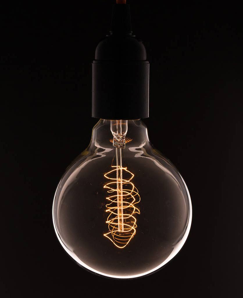 large globe light bulbs with spiral filament against black background