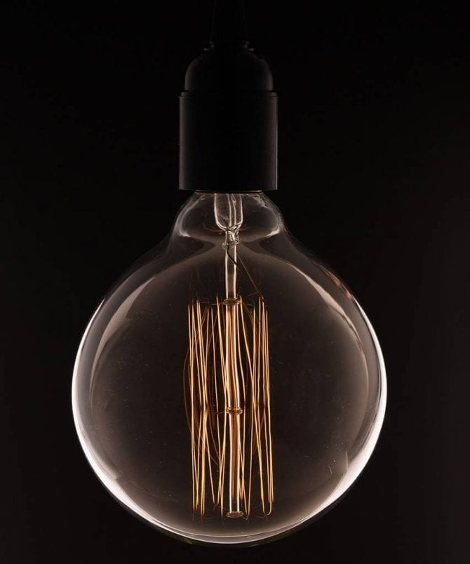 extra large edison bulbs with squirrel cage filament against black background