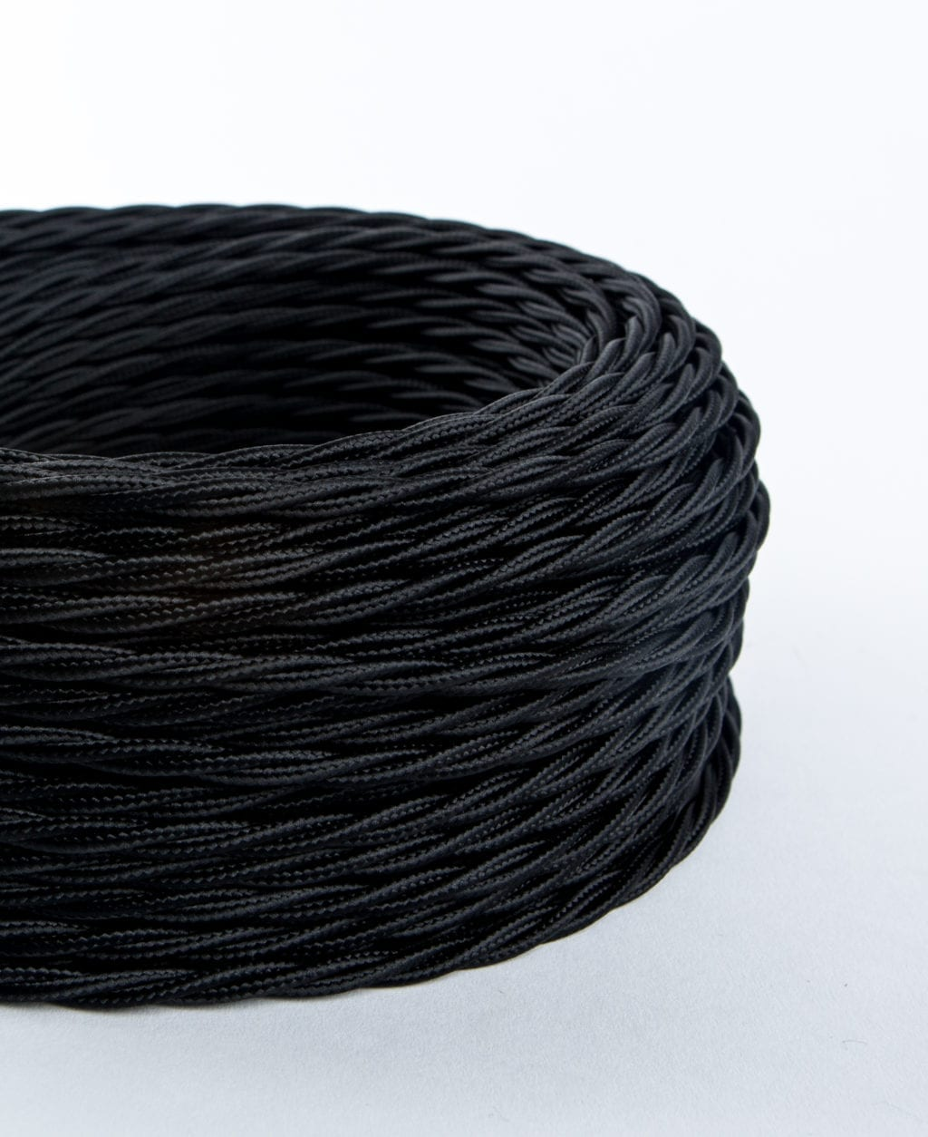 closeup of black twisted fabric cable coil on white background