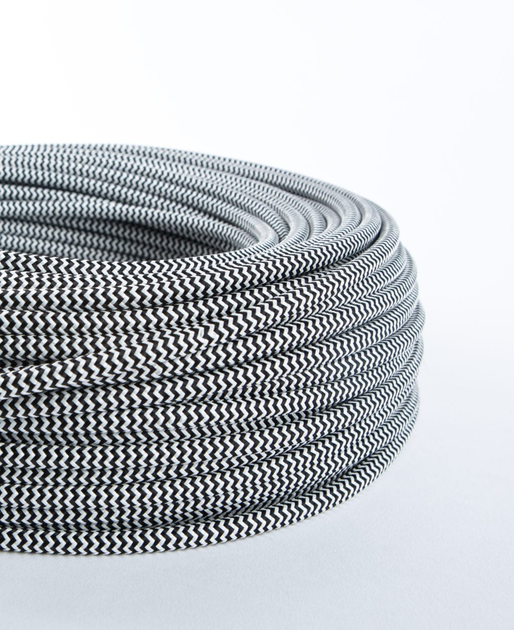 closeup of black and white zig zag fabric cable coil against white background