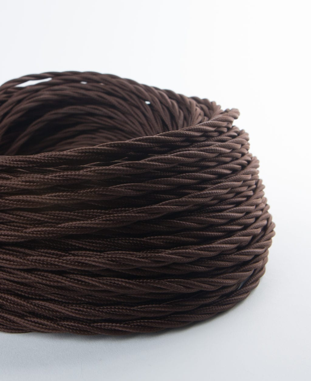 closeup of brown twisted fabric cable coil against white background