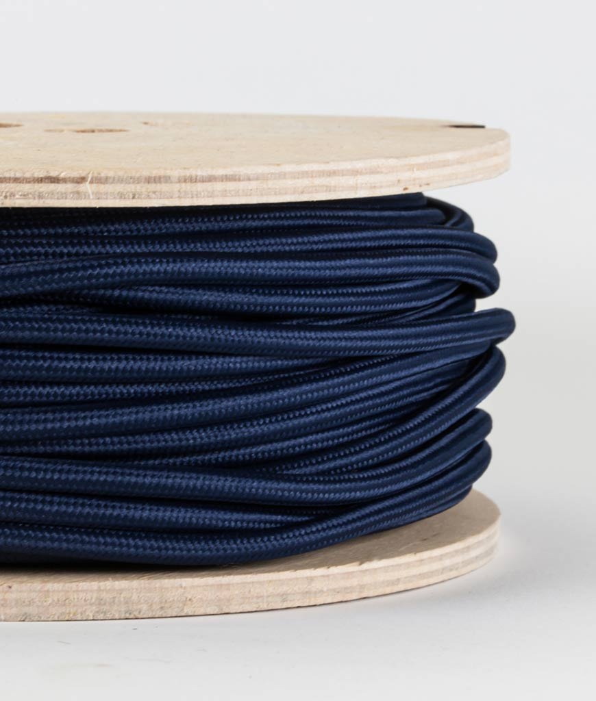 closeup of navy fabric cable on reel against white background