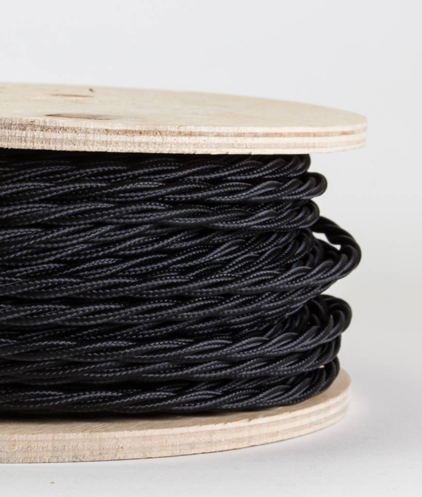 closeup of navy twisted fabric cable on reel against white background