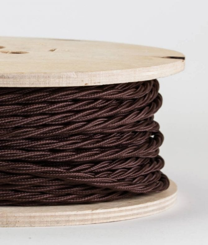 closeup of brown twisted fabric cable on reel against white background