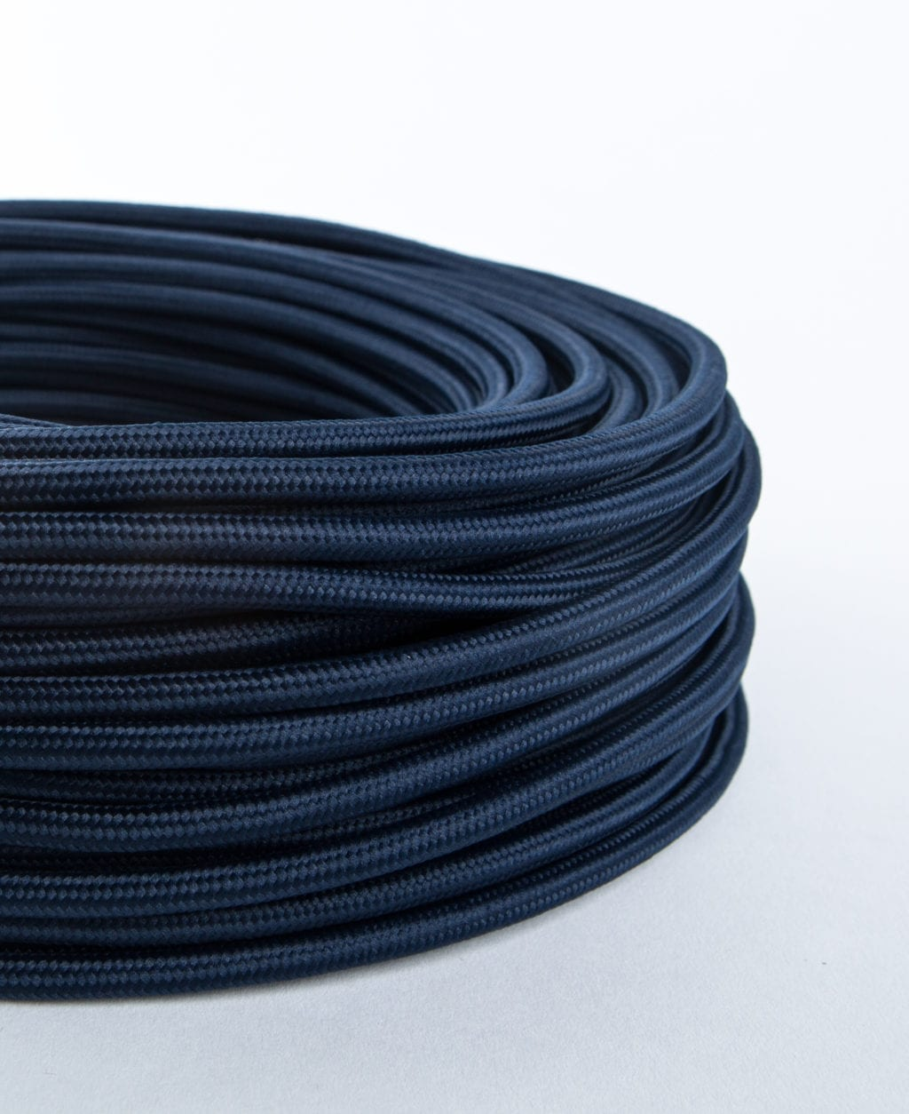 closeup navy blue smooth fabric cable against white background