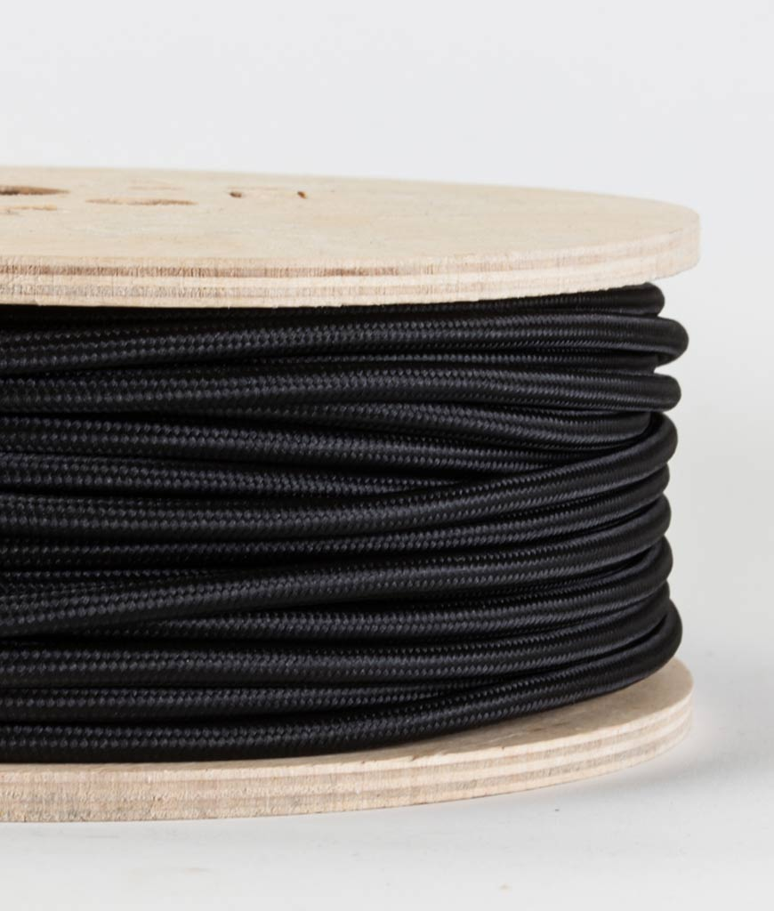 closeup of black fabric cable on reel against white background