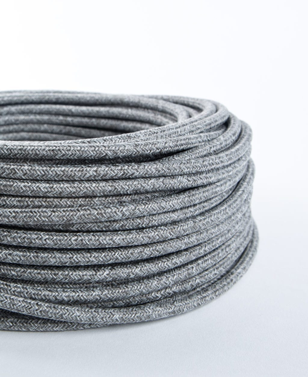 closeup of grey jumper fabric cable coil against white background