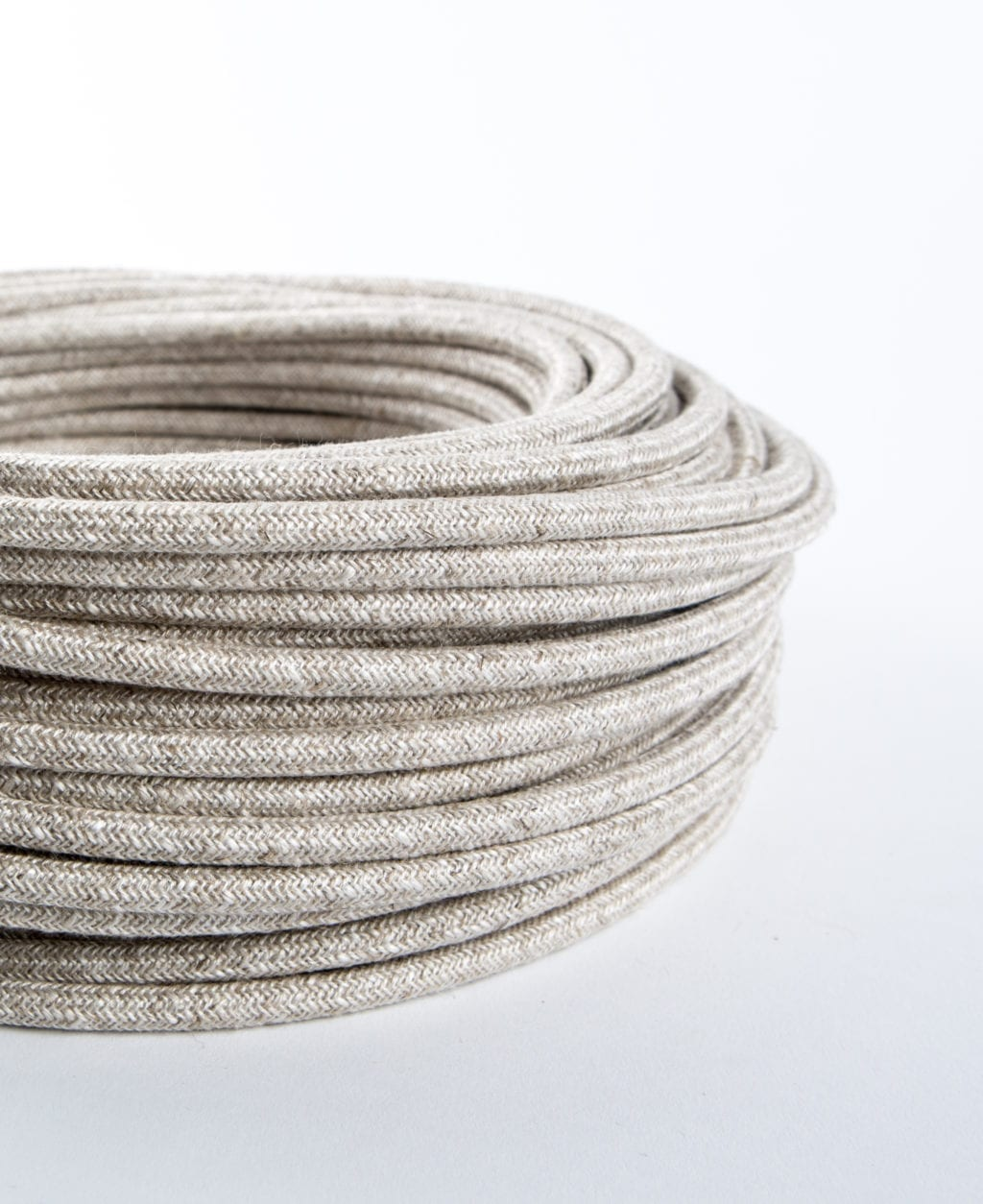 closeup of linen fabric cable coil against white background