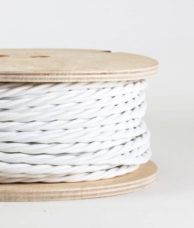 closeup of white twisted fabric cable on reel against white background
