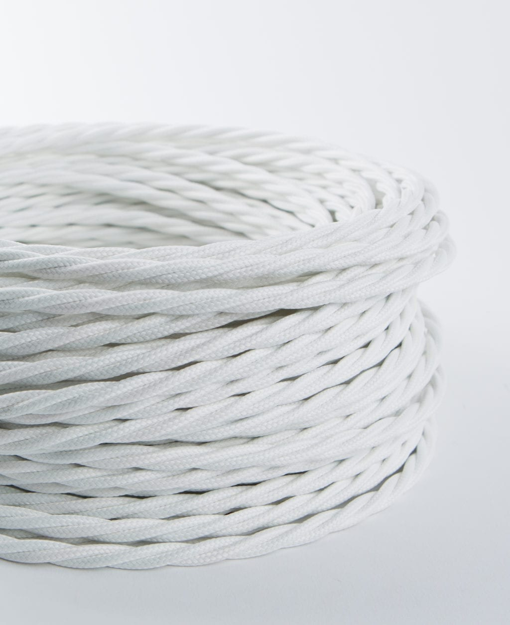 closeup of white twisted fabric cable coil against white background