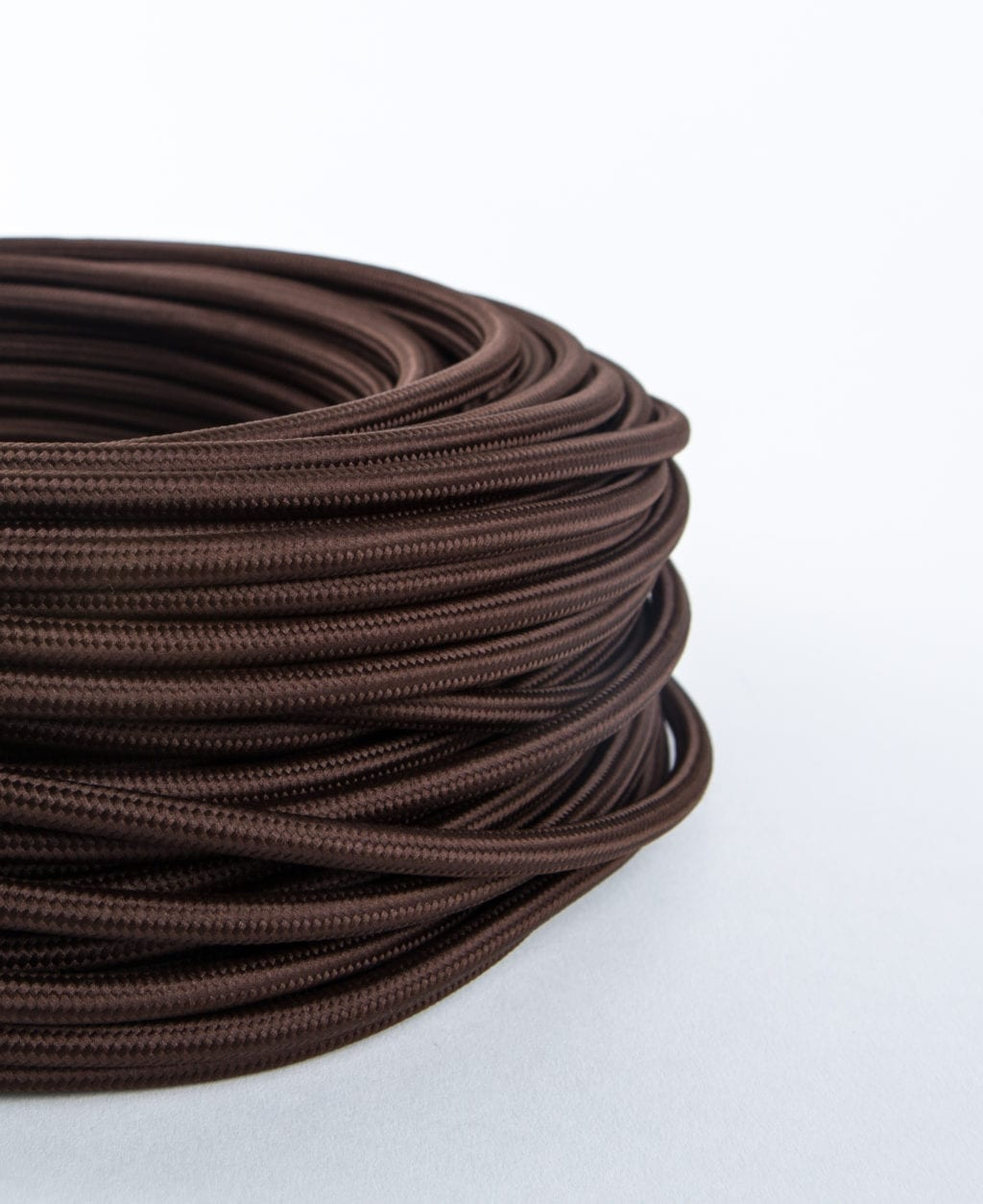 closeup of brown fabric cable coil against white background