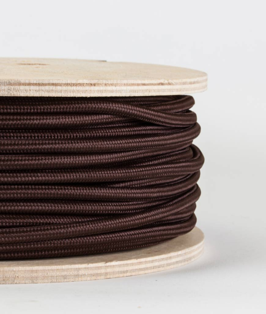 closeup of brown fabric cable on reel against white background
