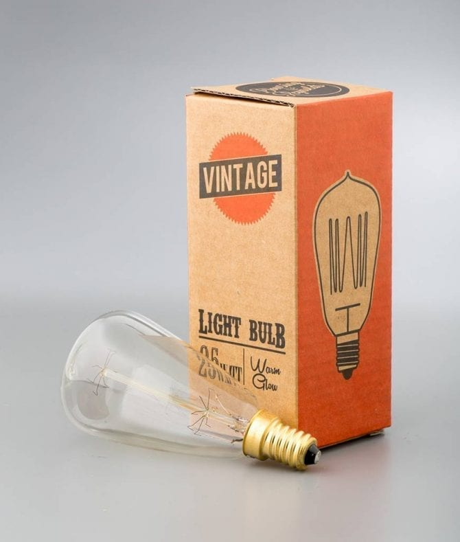 small vintage pear shaped light bulb e14 with squirrel cage filament against white background