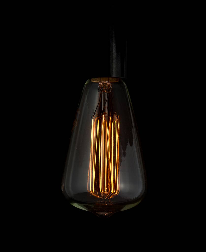 pear shaped light bulb E14 with squirrel cage filament agianst black background