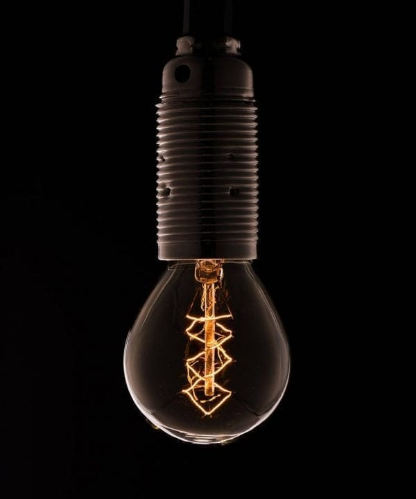 small ball E14 light bulbs with spiral filament with Bakelite bulb holder against black background
