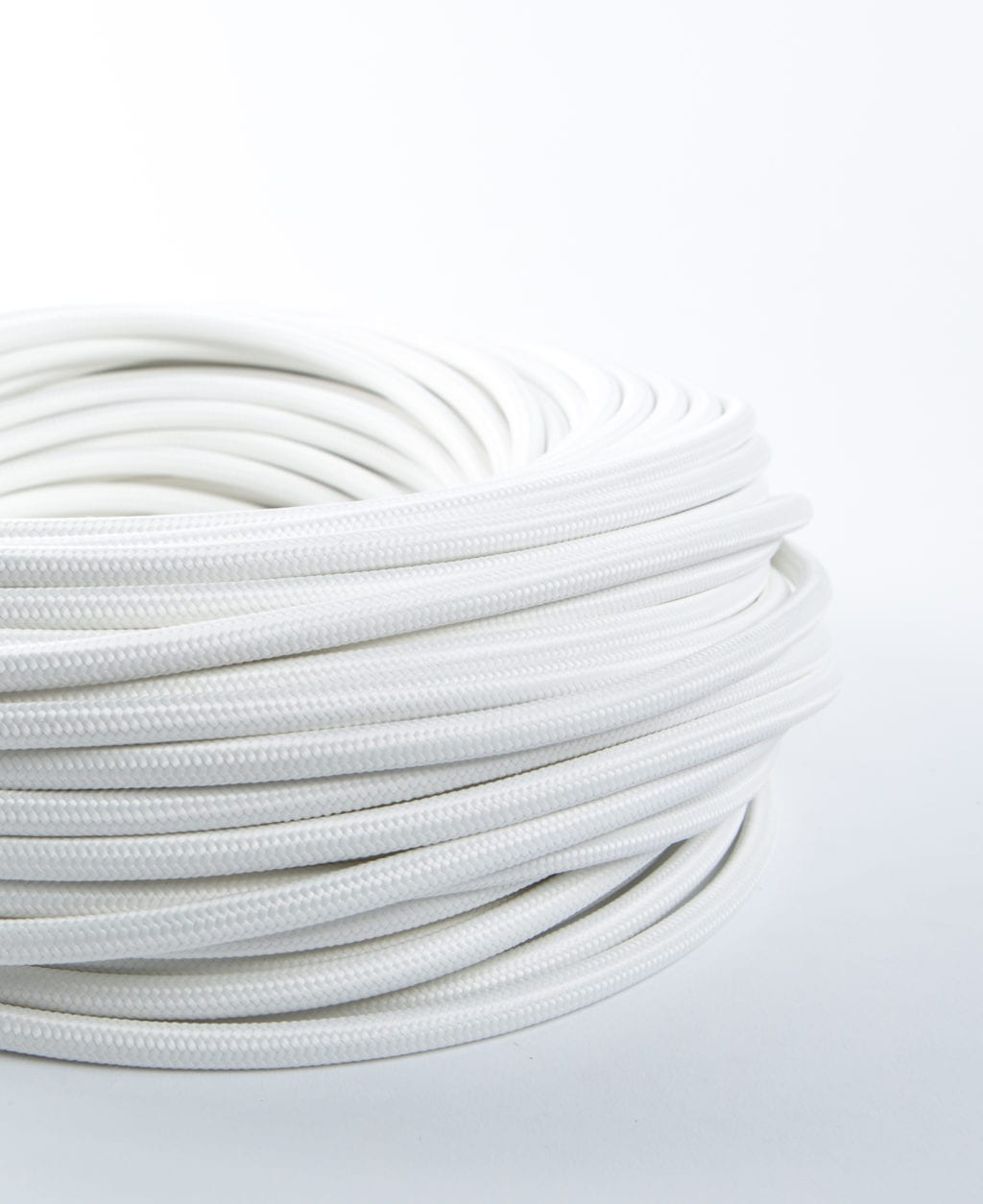 closeup of white fabric cable coil against white background