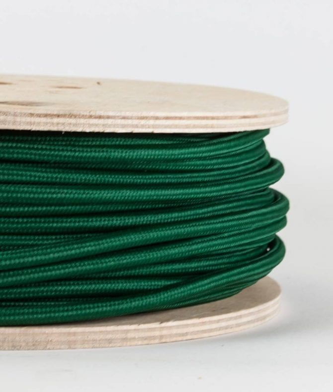 closeup of bottle green fabric cable on reel against white background
