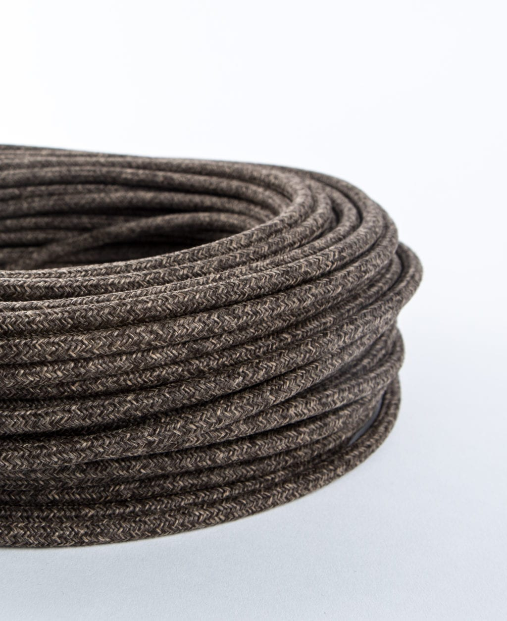 closeup of brown jumper fabric cable coil against white background