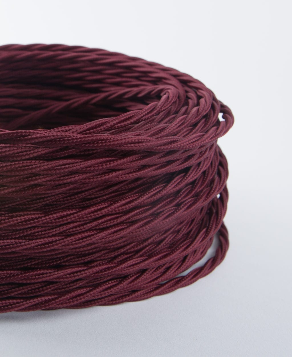 closeup of burgundy twisted fabric cable coil against white background