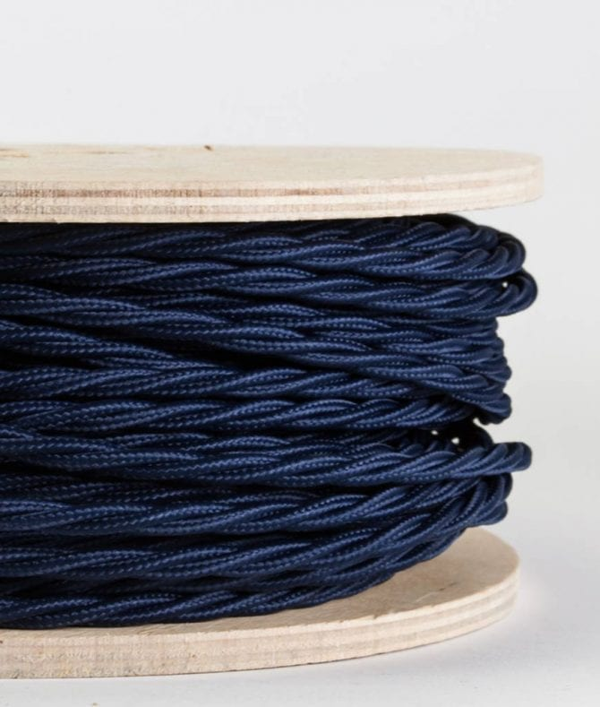 closeup of navy twsited fabric cable on reel against white background