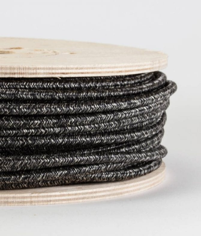 closeup of fisherman's jumper fabric cable on reel against white background