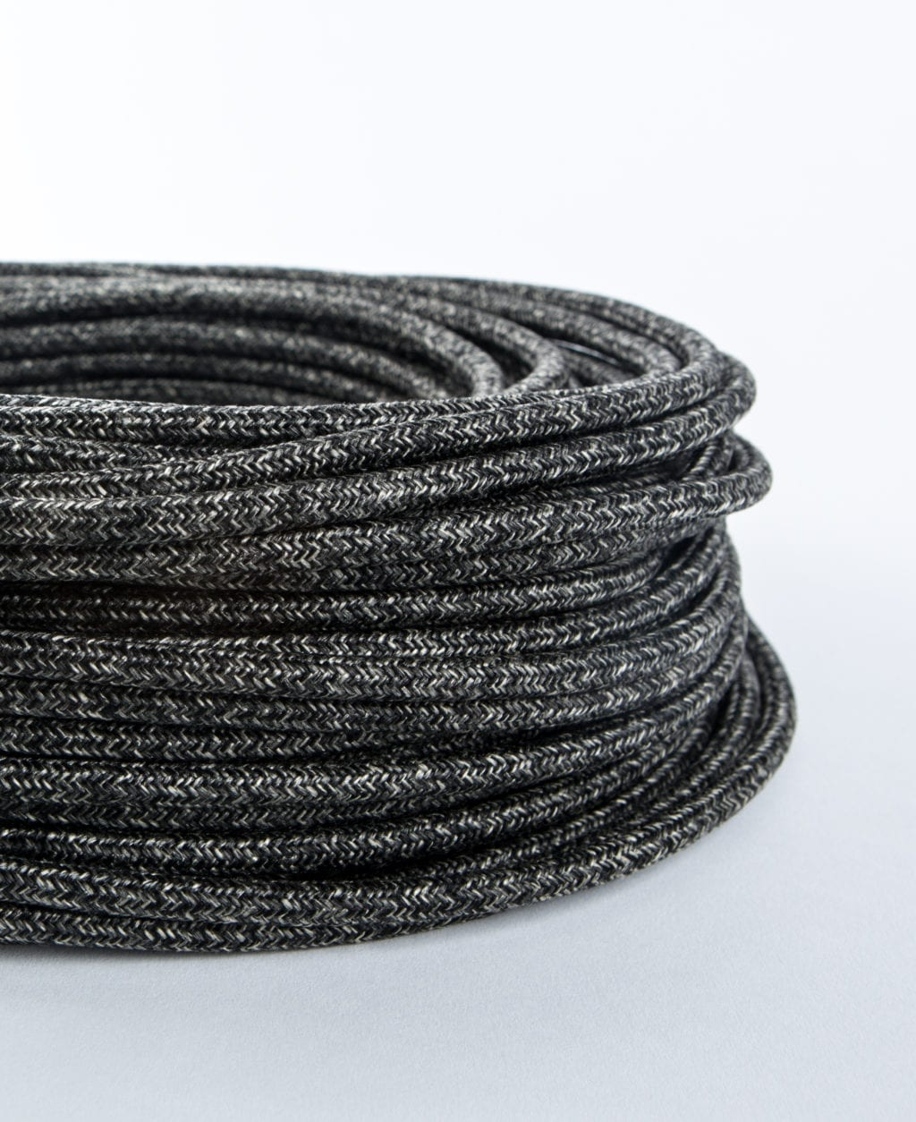 closeup of fisherman's jumper fabric cable coil against white background