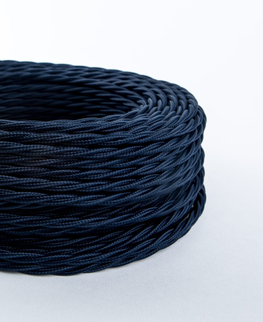 closeup of navy blue twisted fabric cable against white background