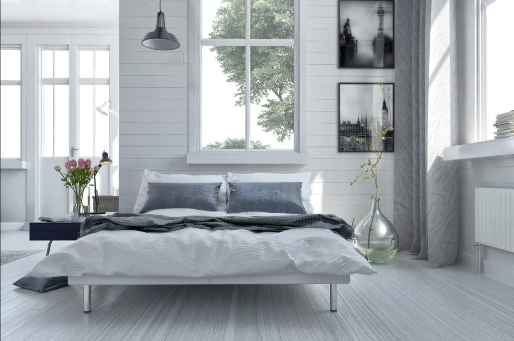 Double divan bed in a light spacious upmarket modern bedroom with large windows and artwork on the walls in grey and white decor
