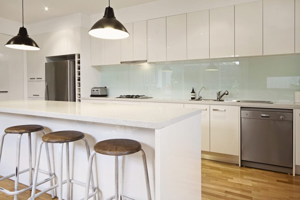 black enamel pendant lights suspended above a white kitchen island in a white kitchen