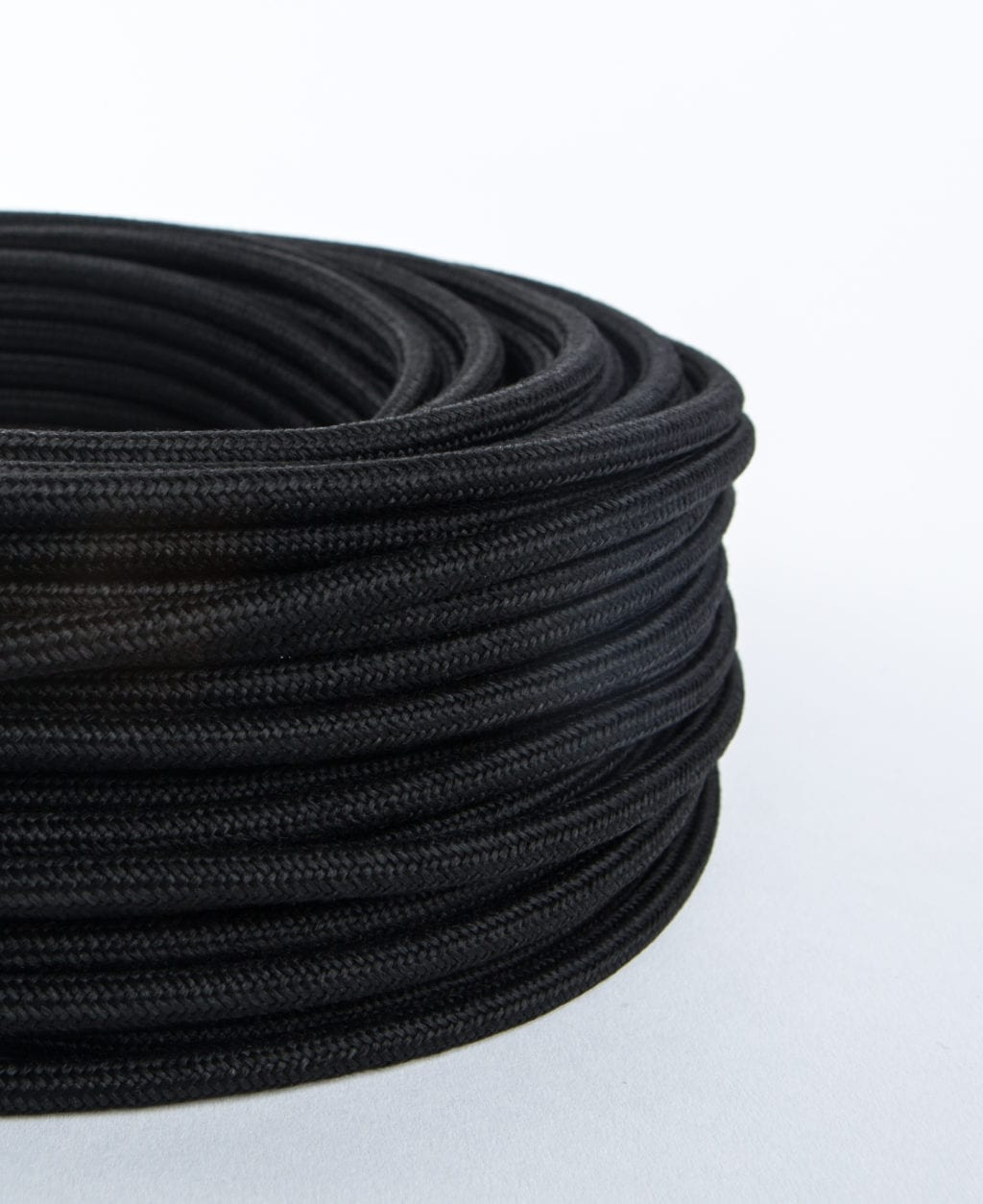 closeup of matt black fabric cable coil against white background