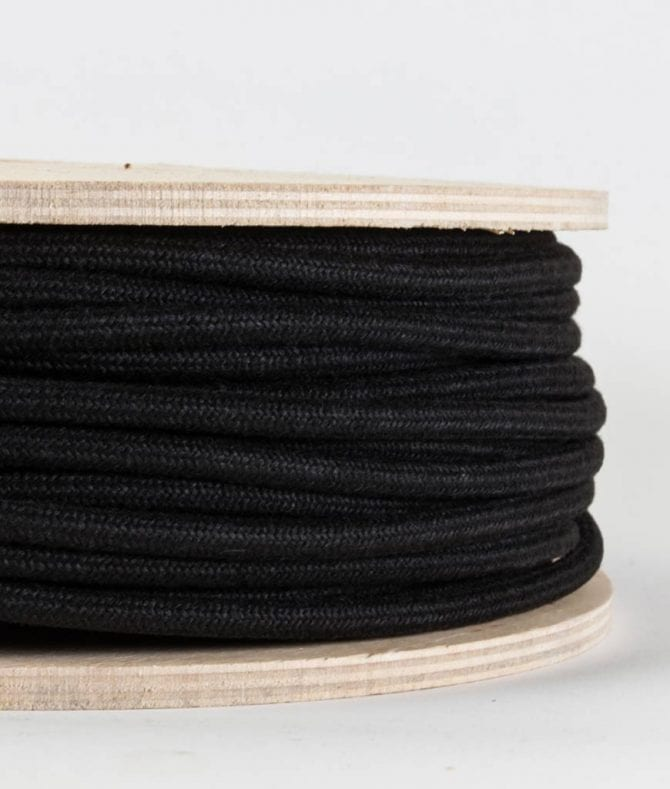 closeup of matt black fabric cable on reel against white background