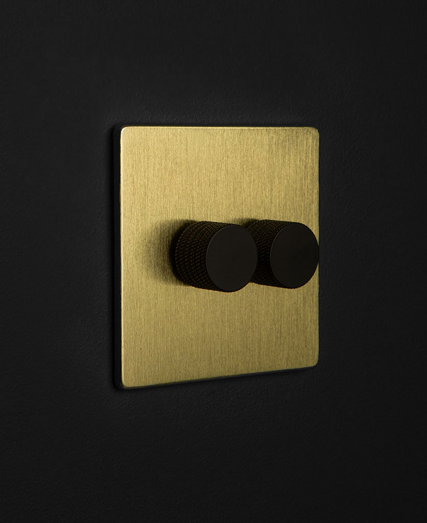 gold dimmer switch with double black dimmer knobs against black wall