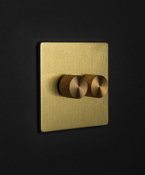 gold dimmer switch with double gold dimmer knobs against black wall
