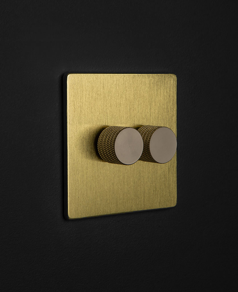 gold dimmer switch with double silver dimmer knobs against black wall