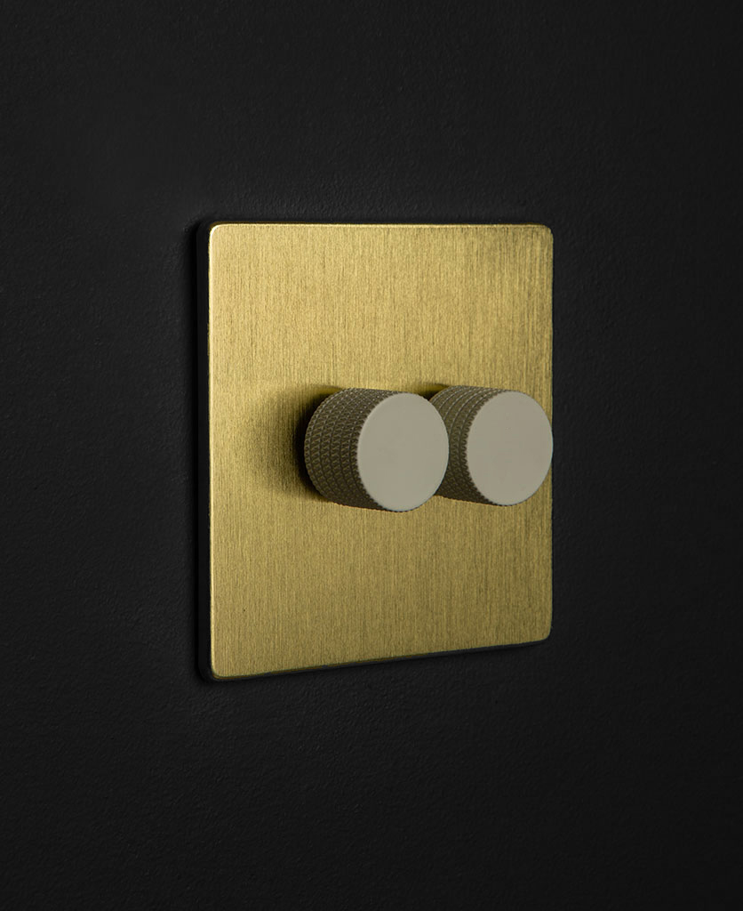 gold dimmer switch with double white dimmer knobs against black wall