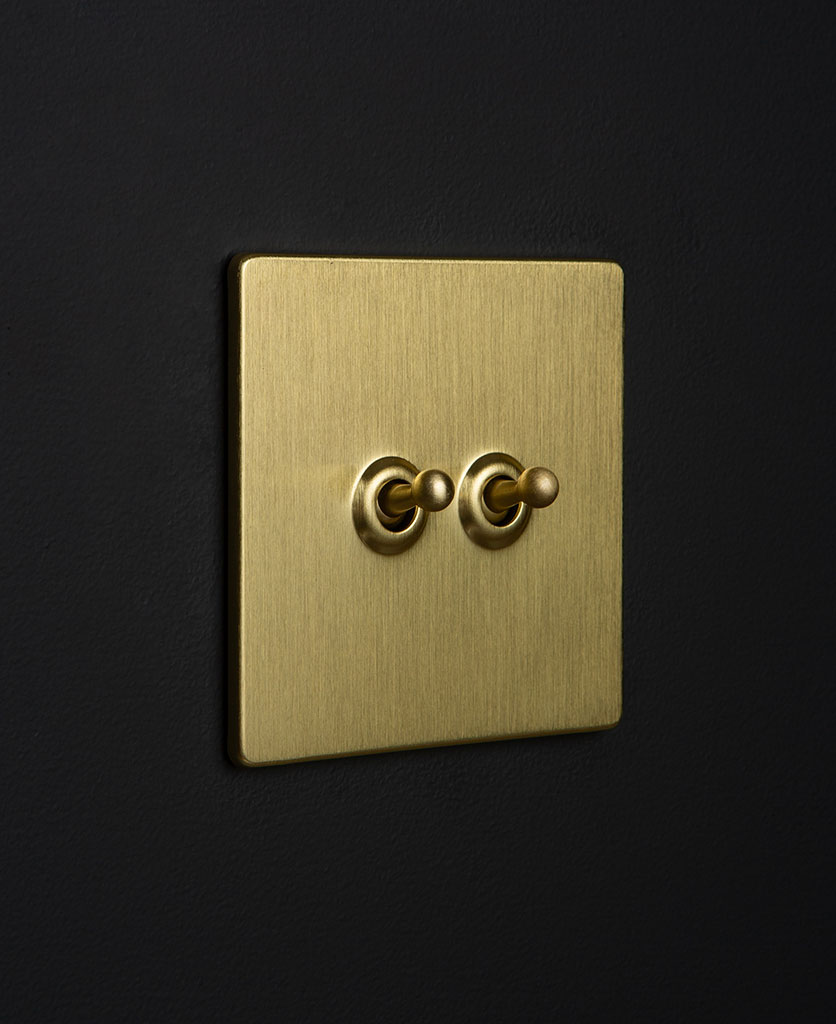 Gold toggle light switches with gold toggle detailing against black wall