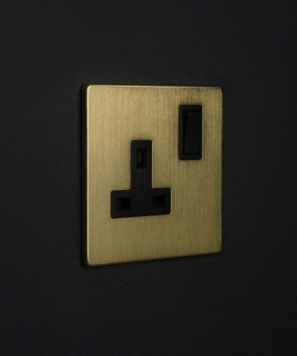 metal plug sockets gold with black inserts against black wall