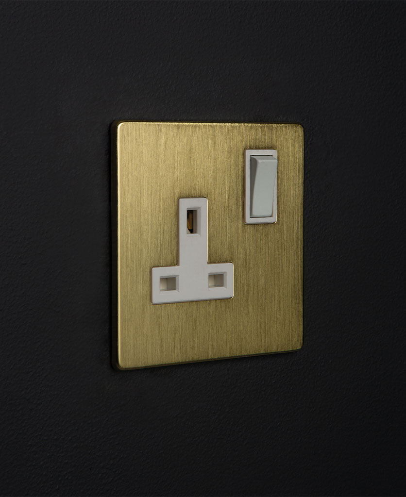 metal plug sockets gold with white inserts against black wall
