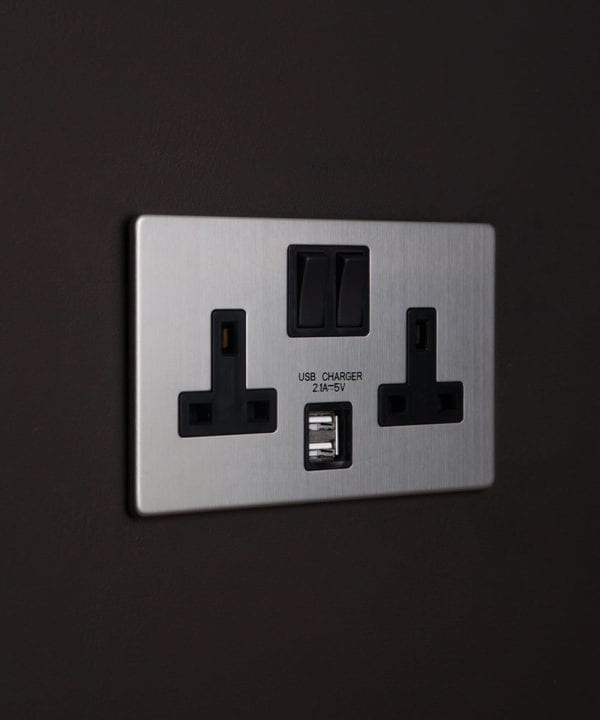 brushed steel USB sockets with double plug socket features silver backplate and black inserts on black wall