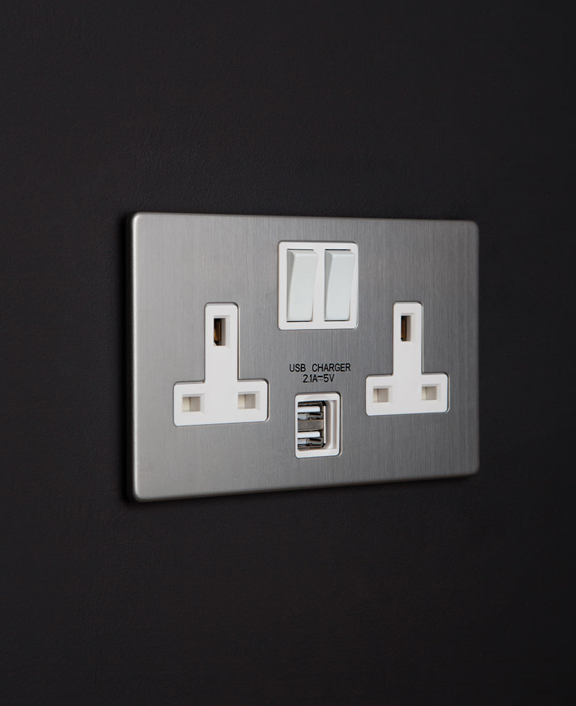 brushed steel USB sockets with double plug socket features silver backplate and white inserts on black wall