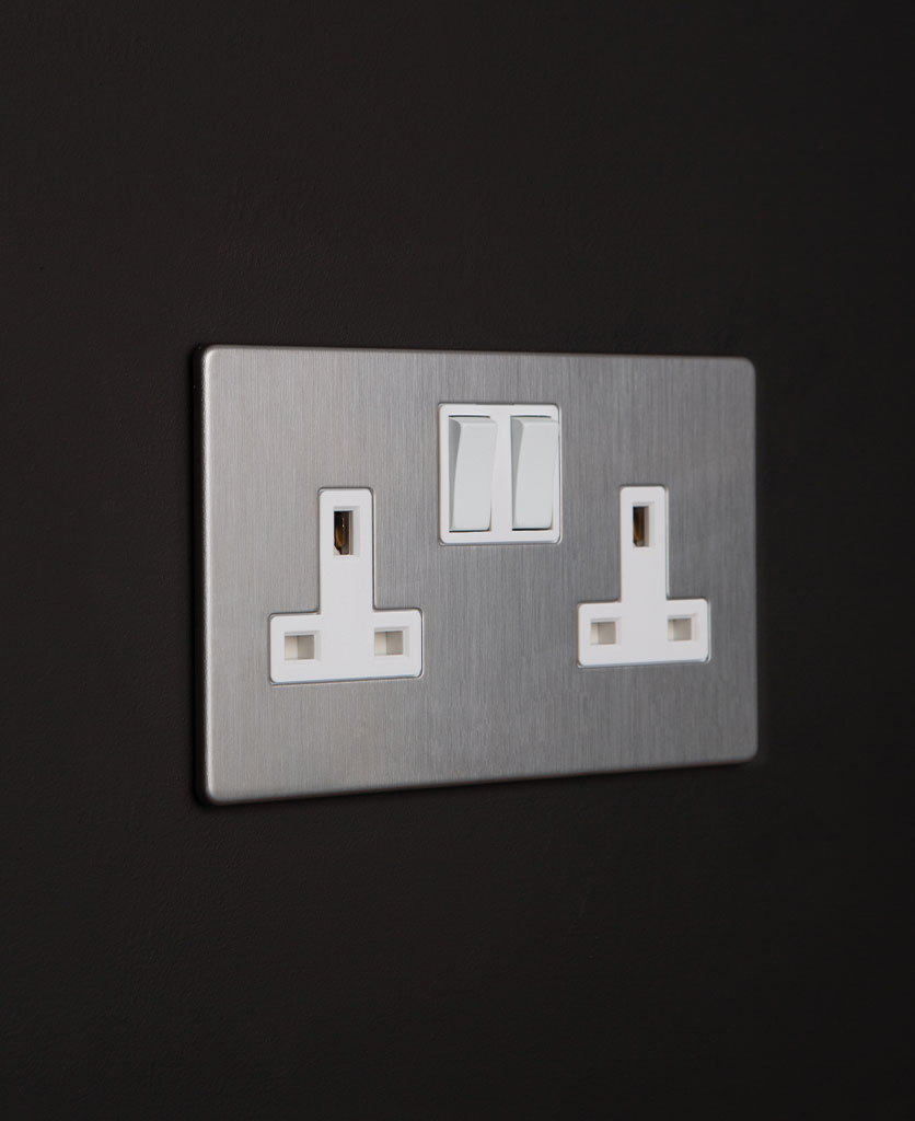 silver double sockets silver socket with white inserts on a black wall