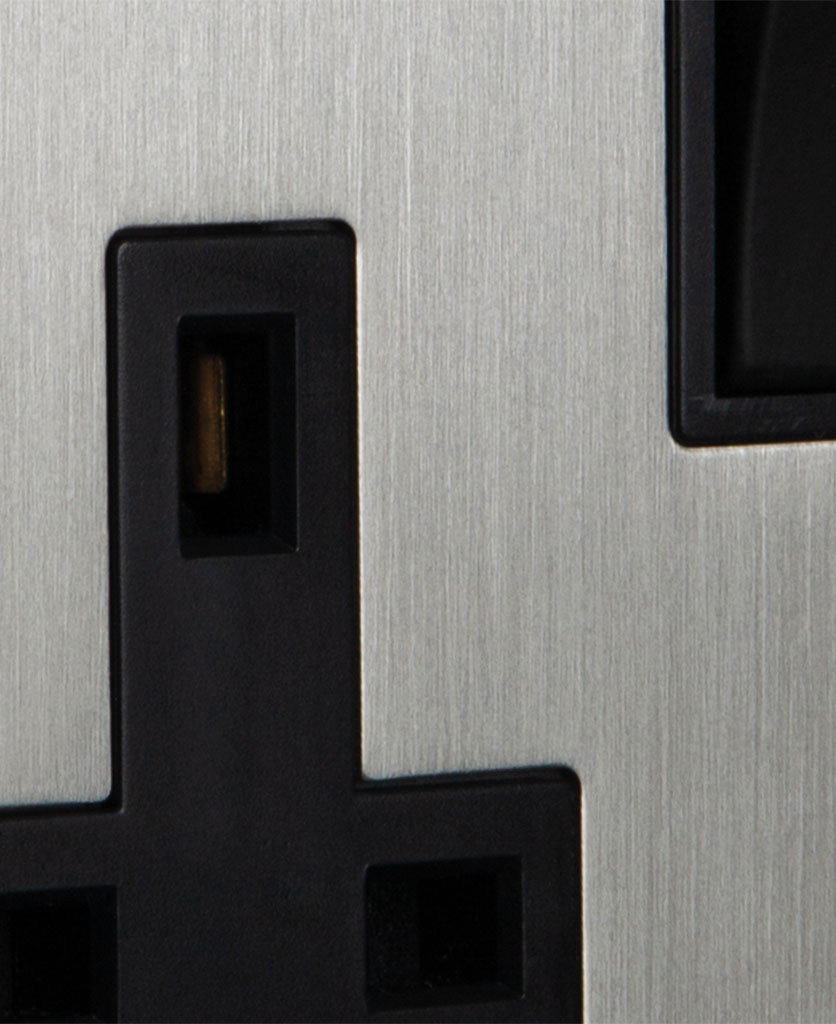 closeup of silver plug socket with black inserts