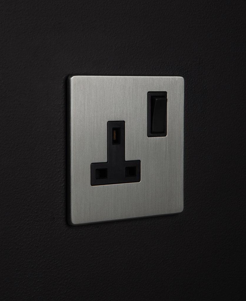 silver sockets single silver plug socket with black inserts on a black wall