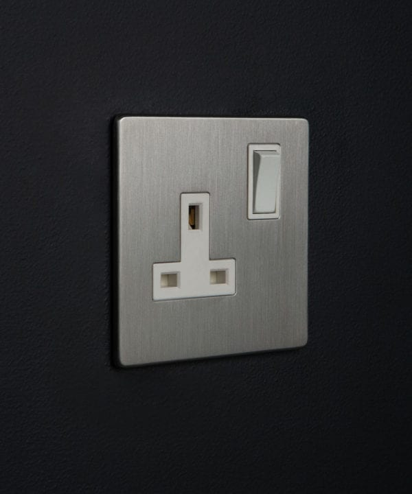 silver sockets single silver plug socket with white inserts on a black wall