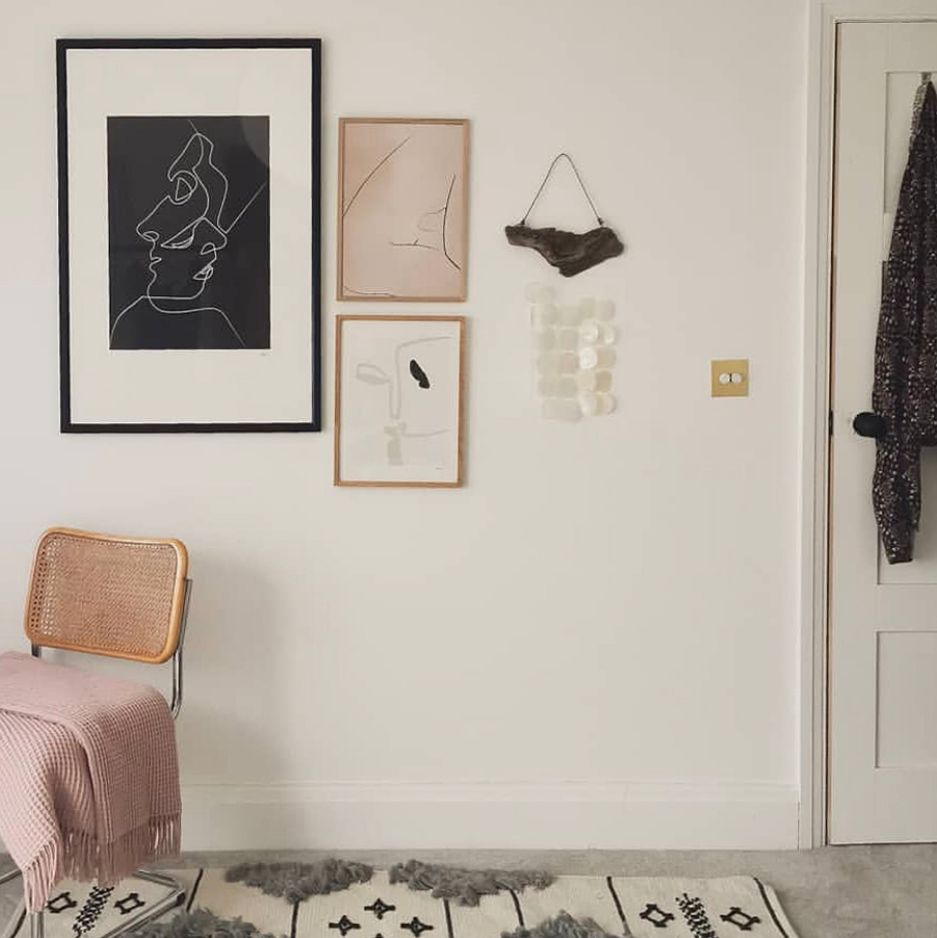 gold double dimmer switch on a white wall alongside framed artwork and a rattan chair with pink throw