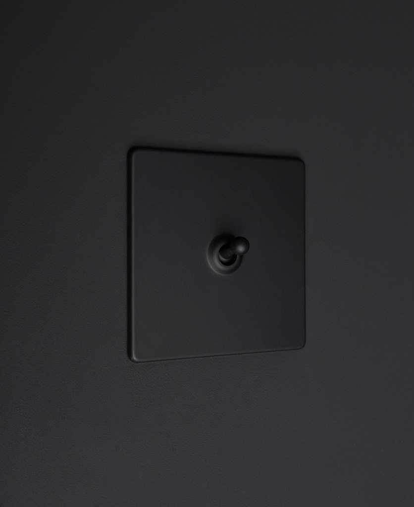 Black one gang toggle switch with black toggle on black background