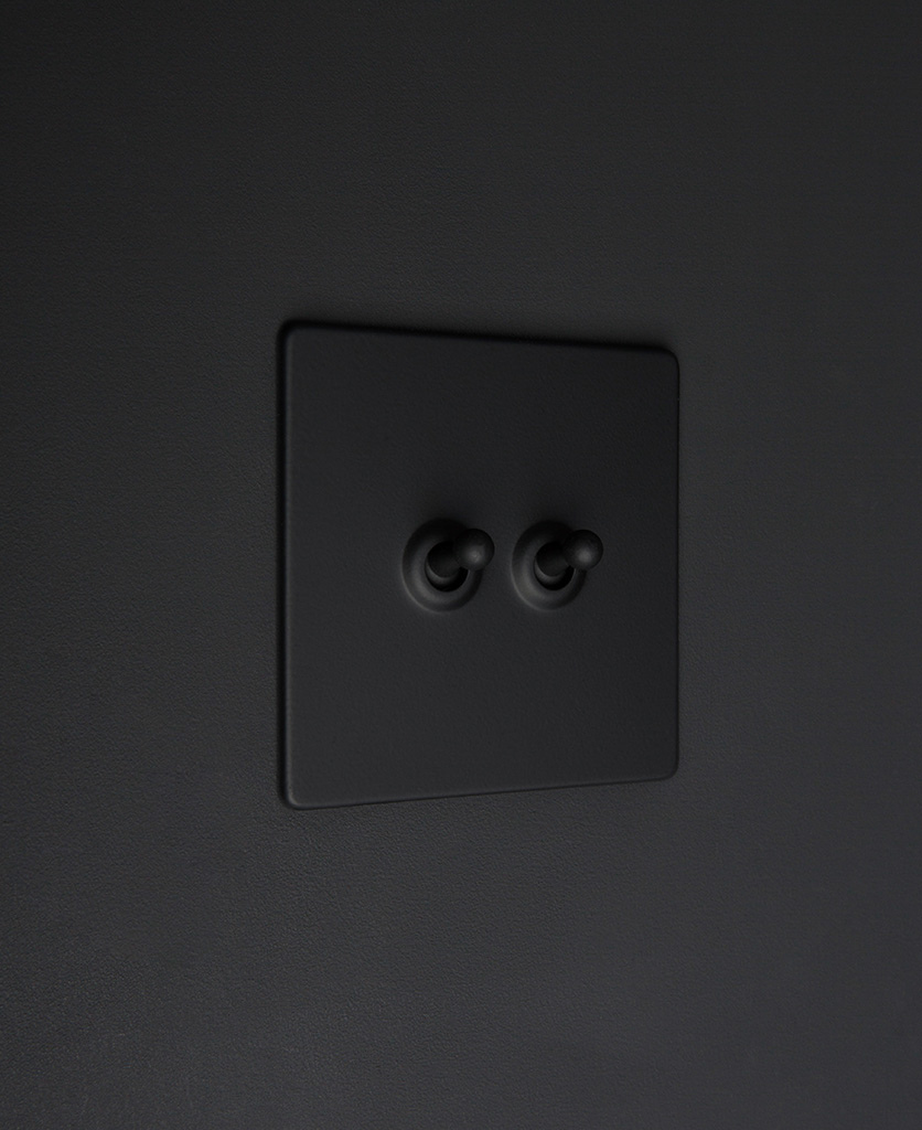 Black two gang toggle switch with black toggles on black background