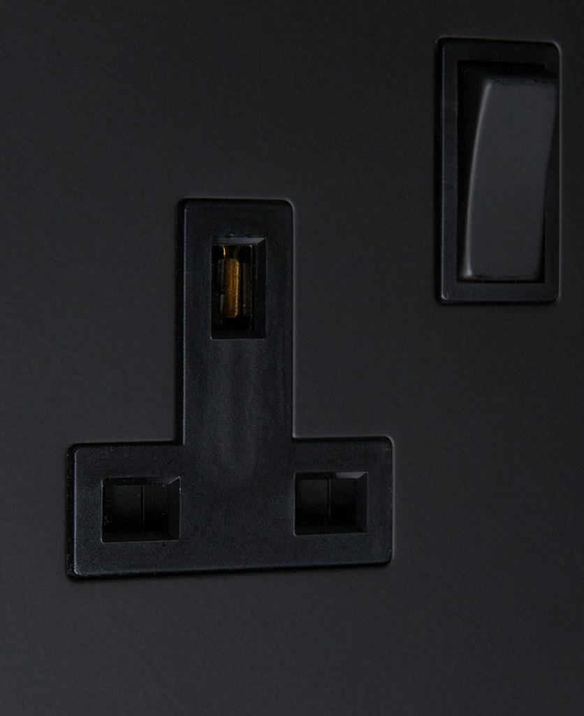 black single 1g plug socket on black background close up