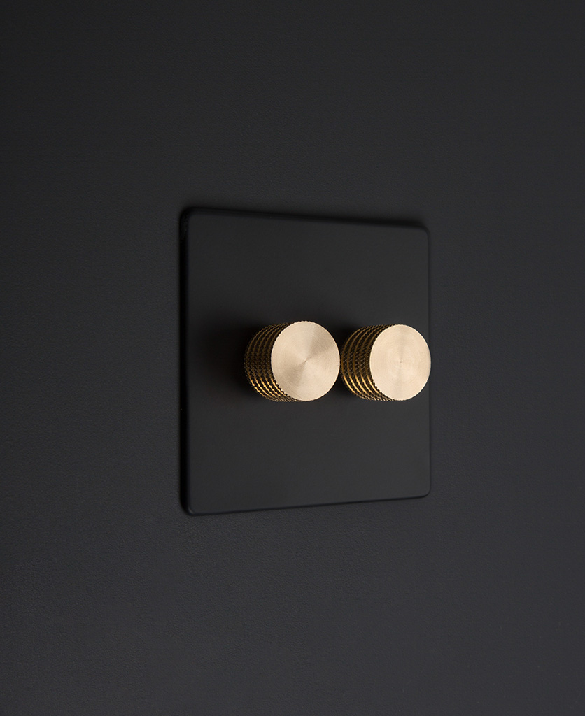 Black standard two gang dimmer switch with gold knobs on black background